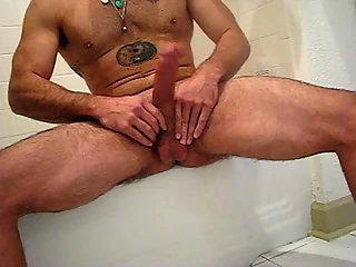 Muscular guy plays with his large cock